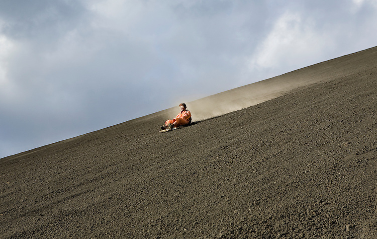 Man boarding down the active Volcano Cerro Negro, Nicaragua
