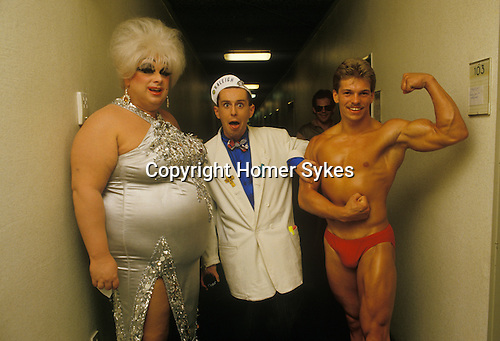 """Holly Johnson, lead singer in the pop band Frankie Goes to Hollywood, during a break in recording a TV special in Hamburg Germany. Seen here with Divine who performer the song """" You Think Your A Man"""" and a local well built young male."""