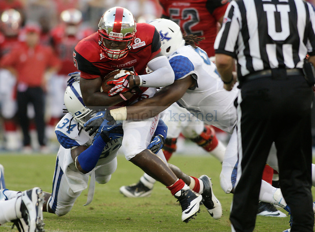 Western Kentucky Hilltoppers running back Antonio Andrews (5) gets tackled by Kentucky Wildcats linebacker Kory Brown (34) and Kentucky Wildcats defensive end Za'Darius Smith (94) during the first half of the UK vs. WKU football game at LP Field in Nashville, Tenn., on Saturday, August 31, 2013. UK lost 35-26. Photo by Tessa Lighty | Staff