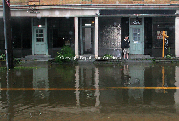 PLYMOUTH, CT.-28 AUGUST 2011-082811JW01-  Vinnie Pawloski waits for the water to recede outside his apartment on Main Street after the Pequabuck River overflowed its banks due to the rainfall from tropical storm Irene Sunday morning.<br /> Jonathan Wilcox Republican American