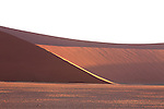 Large red sand dunes loom on the way to Sossusvlei and create abstract sculptures of shape and light.