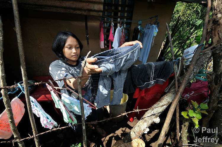 Apple Jane Rapirap hangs clothing to dry outside her home in the village of Maasin, on the southern Philippines island of Mindanao. The ACT Alliance helped people in this village to recover from the 2011 passage of Typhoon Washi, and thus resist their vulnerability to Typhoon Bopha in 2012.