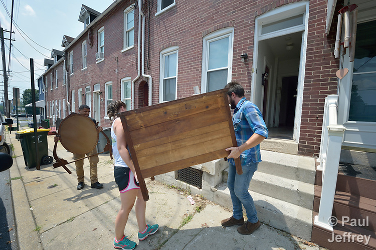 Emilie MacDonald and Luis Ortiz carry a dresser into an apartment in Lancaster, Pennsylvania. They are furnishing what will become home for a refugee family about to arrive in the United States. They work for Church World Service, which resettles refugees in Pennsylvania and other locations in the United States. <br /> <br /> Photo by Paul Jeffrey for Church World Service.