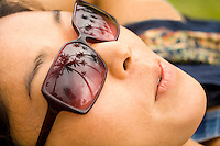 Young woman in hammock at beach wearing aloha shirt, with palm trees reflected in her sunglasses