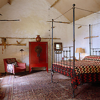 An unadorned wrought iron four-poster bed is covered with a geometric patterned bedspread in this double-height bedroom