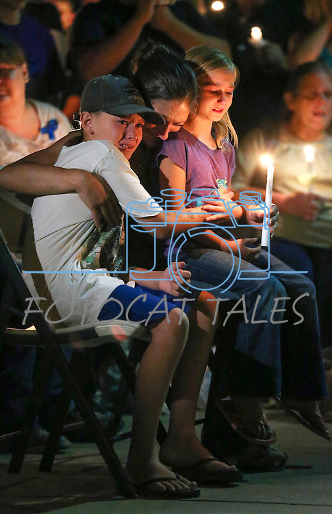 Grief-stricken family members of a Carson City Sheriff's deputy killed in the line of duty early Saturday attend a candlelight vigil in Carson City, Nev., on Saturday, Aug. 15, 2015. Hundreds of residents came out to show their support for the family and department. Photo by Cathleen Allison