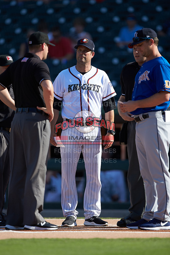 Charlotte Knights manager Mark Grudzielanek (15) meets with Durham Bulls manager Jared Sandberg (22) and the umpiring crew prior to the start of their International League game at BB&T BallPark on July 4, 2018 in Charlotte, North Carolina. The Knights defeated the Bulls 4-2.  (Brian Westerholt/Four Seam Images)