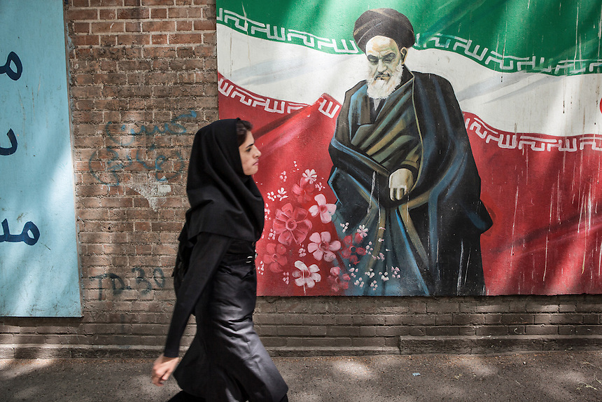 Iranian pass the anti Imam Khomeini murals at the ex U.S Embassy (now called Den of Espionage) in Tehran.