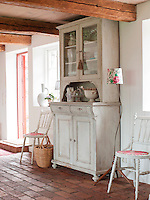 In the spacious kitchen/dining area of the farmhouse, a traditional feel has been retained with old pieces of furniture, such as the cabinet and stick chairs