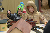 NWA Democrat-Gazette/ANDY SHUPE<br /> Tyler Livermore, 4, (left) of Prairie Grove and friend Brianna Presley, 5, of Huntsville reach to take candy canes from an electric train on display Saturday, Dec. 1, 2018, during the annual Christmas Train at the Arkansas &amp; Missouri Railroad in Springdale. The event features a 40-minute ride to Johnson and back aboard a 1940s-era passenger car with Christmas carols. Santa Claus sat for photographs with families in a caboose while games and pony rides were available at the depot.