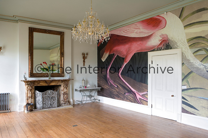 Large drawing room with fireplace and mirror above it.