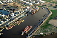An aerial view of a ship and barges at the docks of a petrochemical refinery; storage structures dot the industrial landscape. Houston, Texas.