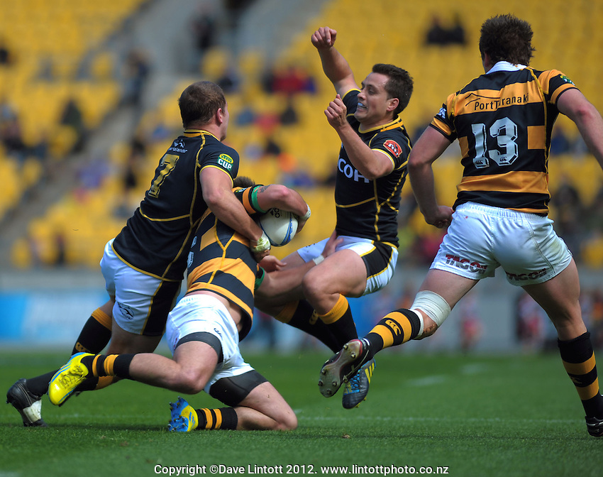 Scott Fuglistaller and Tim Bateman tackle Andre Taylor during the ITM Cup rugby union match between Wellington Lions and Taranaki at Westpac Stadium, Wellington, New Zealand on Sunday, 14 October 2012. Photo: Dave Lintott / lintottphoto.co.nz