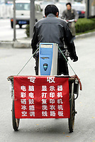 A collector of used computer products, home appliances & ink catridges, cycles in street of Zhongguancun, Beijing, China..05-NOV-03