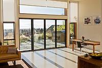 Margarido House, Oakland, California - LEED. Sliding glass doors opening living room to patio overlooking San Francisco Bay