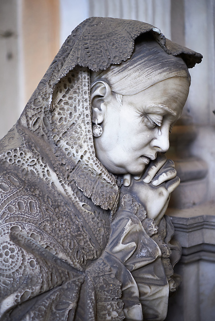 Picture and image of the stone sculpture of a mouring women in the Bourgeois Realistic style. Badaracco Tomb sculpted by G Moreno 1878. The monumental tombs of the Staglieno Monumental Cemetery, Genoa, Italy