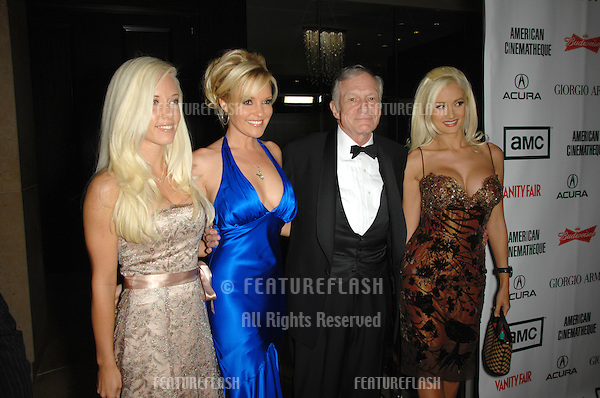 HUGH HEFNER & playmates at the 2006 American Cinematheque Gala where George Clooney was presented with the 21st Annual American Cinematheque Award at the Beverly Hilton Hotel..October 13, 2006  Los Angeles, CA.Picture: Paul Smith / Featureflash