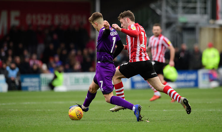Grimsby Town's Jake Hessenthaler under pressure from Lincoln City's Shay McCartan<br /> <br /> Photographer Chris Vaughan/CameraSport<br /> <br /> The EFL Sky Bet League Two - Lincoln City v Grimsby Town - Saturday 19 January 2019 - Sincil Bank - Lincoln<br /> <br /> World Copyright &copy; 2019 CameraSport. All rights reserved. 43 Linden Ave. Countesthorpe. Leicester. England. LE8 5PG - Tel: +44 (0) 116 277 4147 - admin@camerasport.com - www.camerasport.com