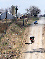 A horse and buggy shares a gravel road with an automobile south of Drakesville in southeast Iowa's Davis County.   It is among only a handful of rural Iowa counties in the 2010 Census to gain population (2.4 percent).  Much of that population growth is due to a steadily growing Amish population.  (Christopher Gannon/The Des Moines Register)
