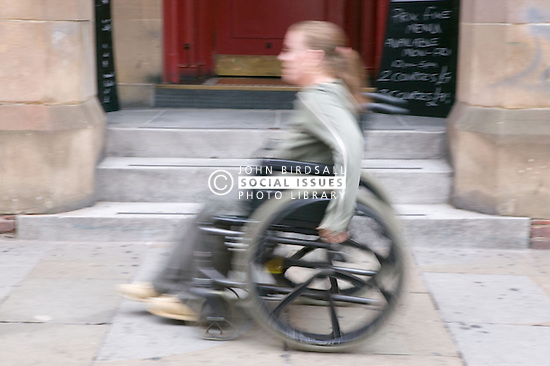 Young wheelchair user moving past a flight of steps which she is unable to access,