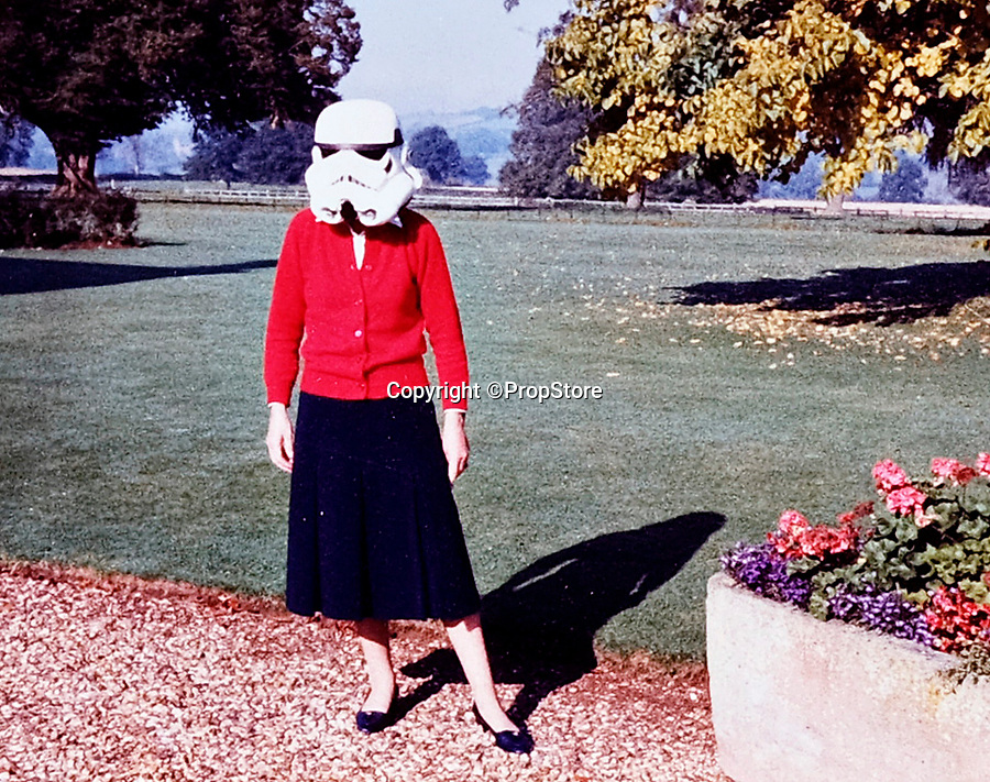 BNPS.co.uk (01202 558833)<br /> Pic: PropStore/BNPS<br /> <br /> Anne Hawkins trys on the helmet at the event in rural Northamptonshire in 1978.<br /> <br /> A Stormtrooper helmet from the first Star Wars film has sold for almost £200,000 by a relative of a British country squire.<br /> <br /> Captain Robert Hawkins and his wife Anne were gifted the iconic helmet for staging the Star Wars Cross Country Team Event at their English manor house in 1978.<br /> <br /> The bizarre equestrian event was attended by Carrie Fisher, who played Princess Leia, Darth Vader actor David Prowse, Peter Mayhew, who played Chewbacca, and football pundit Jimmy Hill.