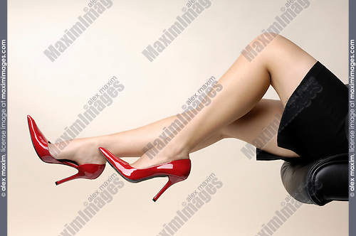 Sexy businesswoman legs in red high-heel shoes