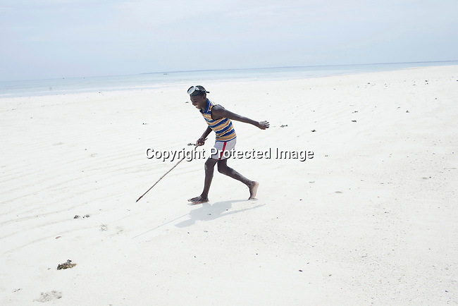 PEMBA, TANZANIA - DECEMBER 7 : Hamissi Usi, age 15, chases a crab on a remote island on December 7, 2010 on Pemba, Tanzania. He works as a fisherman. He doesn't go to school but lives with his parents and siblings in the small village of Tumbe. (Photo by: Per-Anders Pettersson)