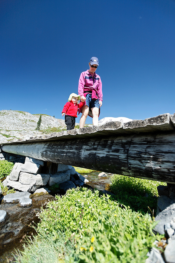Mother and daughter cross bridge on Mazama Ridge Trail, Mount Rainier National Park, Washington, USA