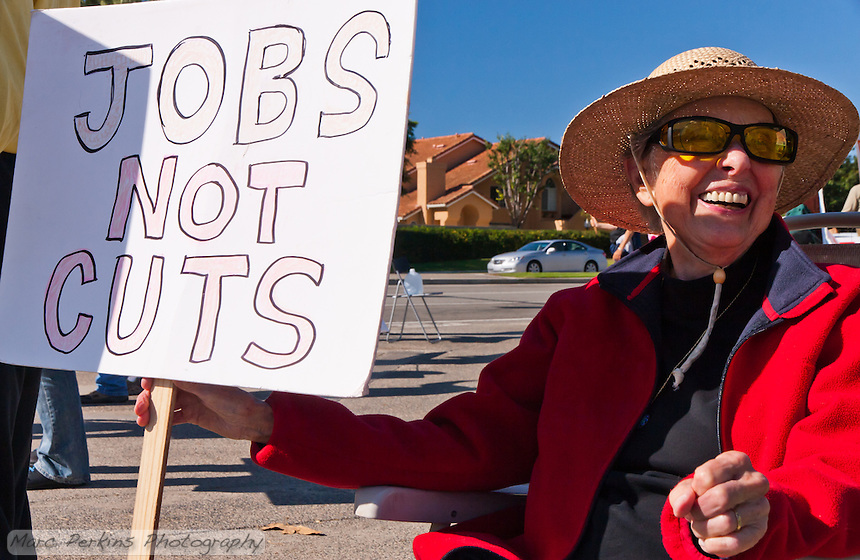 "Cov sits in a lawn chair holding a ""Jobs not cuts"" sign at the Occupy Orange County, Irvine camp on November 5."