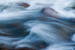 A photo of blurred moving water and rocks in the Truckee River in California