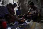 Mahmod Ahmad Issa and his male family members eat Iftar meal during Ramadan in his cave in Jenba a Palestinian town of 50 families seats in an area called by the IDF as &ldquo;Firing Zone 918&rdquo; and is located in the southern Hebron hills near the town of Yatta.  Spread over 30,000 dunams, it includes twelve Palestinian villages.  According to OCHA figures, 1,622 people lived in the area in 2010, and according to local residents the number of inhabitants currently stands at about 1,800. For over a decade, the residents of twelve uniquely traditional Palestinian villages in the area of Masafer-Yatta in the south Hebron hills have lived under the constant threat of demolition, evacuation, and dispossession.<br />