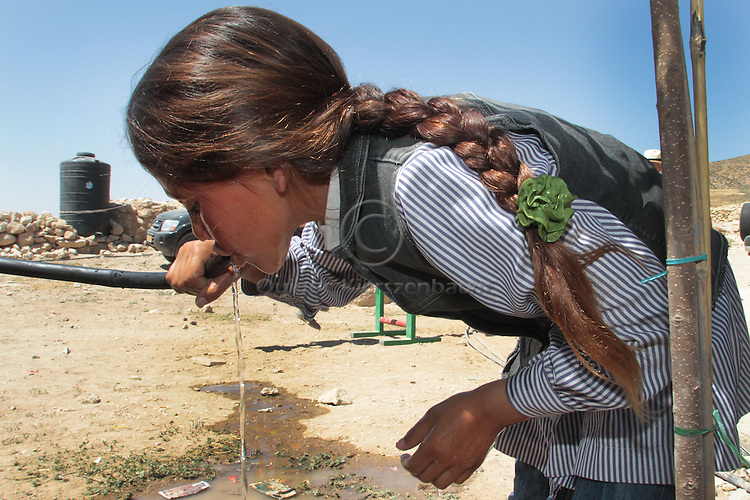 A Palestinian girl drinks water from a pipe at Jenba's school in the South Hebron Hills, Jenba a Palestinian town of 50 families seats in an area called by the IDF as &ldquo;Firing Zone 918&rdquo; and is located in the southern Hebron hills near the town of Yatta.  Spread over 30,000 dunams, it includes twelve Palestinian villages.  According to OCHA figures, 1,622 people lived in the area in 2010, and according to local residents the number of inhabitants currently stands at about 1,800. For over a decade, the residents of twelve uniquely traditional Palestinian villages in the area of Masafer-Yatta in the south Hebron hills have lived under the constant threat of demolition, evacuation, and dispossession.<br /> The State's insistence on evacuation of Firing Zone 918 in part or in whole, if acceptance by the HCJ, might result in an immediate humanitarian disaster for almost two thousand souls, the destruction of villages, and the eradication of a remarkable way of life that has endured for centuries. Photo by Quique Kierszenbaum.