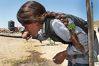"A Palestinian girl drinks water from a pipe at Jenba's school in the South Hebron Hills, Jenba a Palestinian town of 50 families seats in an area called by the IDF as ""Firing Zone 918"" and is located in the southern Hebron hills near the town of Yatta.  Spread over 30,000 dunams, it includes twelve Palestinian villages.  According to OCHA figures, 1,622 people lived in the area in 2010, and according to local residents the number of inhabitants currently stands at about 1,800. For over a decade, the residents of twelve uniquely traditional Palestinian villages in the area of Masafer-Yatta in the south Hebron hills have lived under the constant threat of demolition, evacuation, and dispossession.<br />
