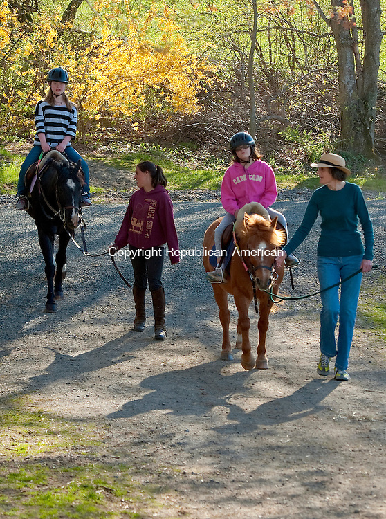 ROXBURY, CT 03 MAY 2013--050313JS09--Alicia Crossley, 13, left, and Anna Bialak, 12, both of Bridgewater, come back from a ride Friday at Little Britches therapeutic riding center in Roxbury. Accompanying them on their ride was instructor Samantha Sola, and program director Stuart Daly.  To honor the memory of Betty Lou McClogin, co-founder of Little Britches, a group has organized a 5K run/walk to raise money for the program. The event will be on Sunday, May 19th in Bridgewater with registration beginning at 8 a.m. with the race going off at 9:30 a.m. There will also be a kids fun run at 11:00 a.m.. Jim Shannon Republican-American