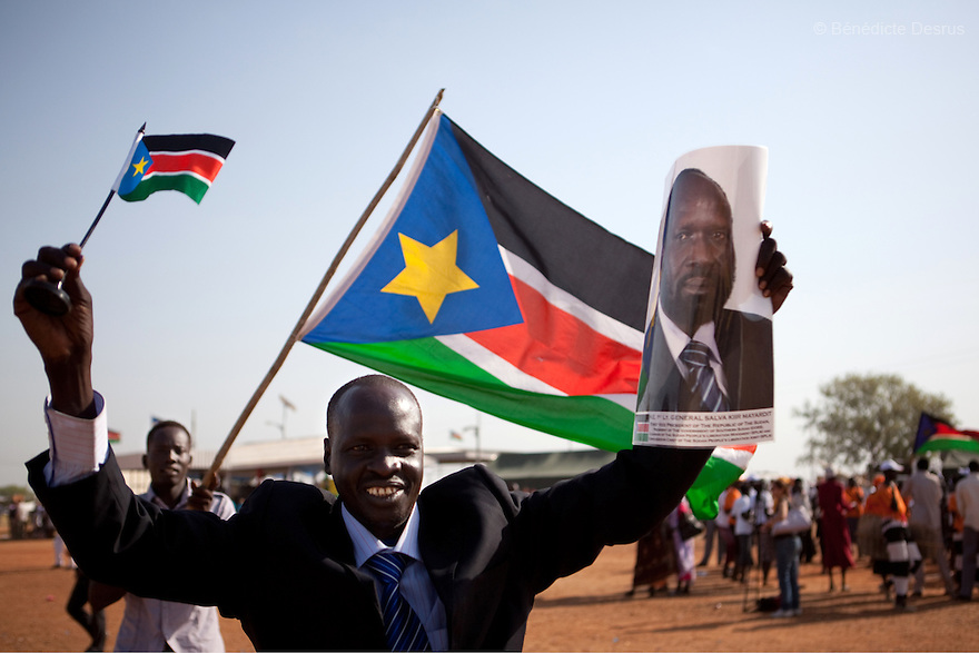 Sunday 9 january 2011 - Juba, Sudan - Southern Sudaneses wave a South Sudan flag and a photo of Salva Kiir Mayardit during the referendum at the John Garang memorial mausoleum where a polling station is being set up in Juba. About four million Southern Sudanese voters began casting their ballots Sunday in a weeklong referendum on independence that is expected to split Africa's largest nation in two. Photo credit: Benedicte Desrus