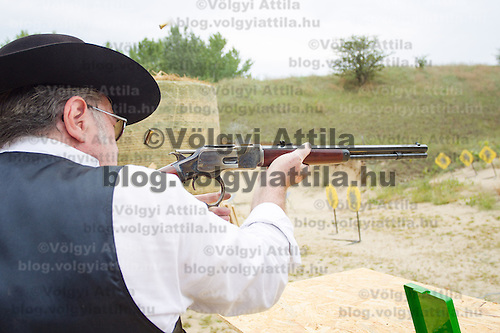 Participant rapid fires his weapon during the Cowboy Action Shooting European Championship in Dabas, Hungary on August 11, 2012. ATTILA VOLGYI