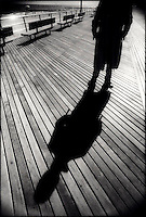 Man's shadow on boardwalk
