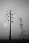 Large transmission tower with power lines in valley with early morning fog