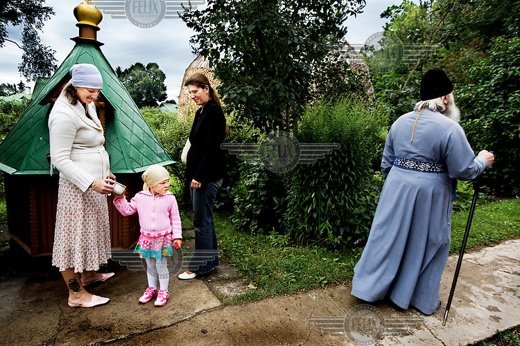A Russian orthodox priest passes pilgrims on their way to the Puhtitsa convent. 160 nuns and novices live in the convent.