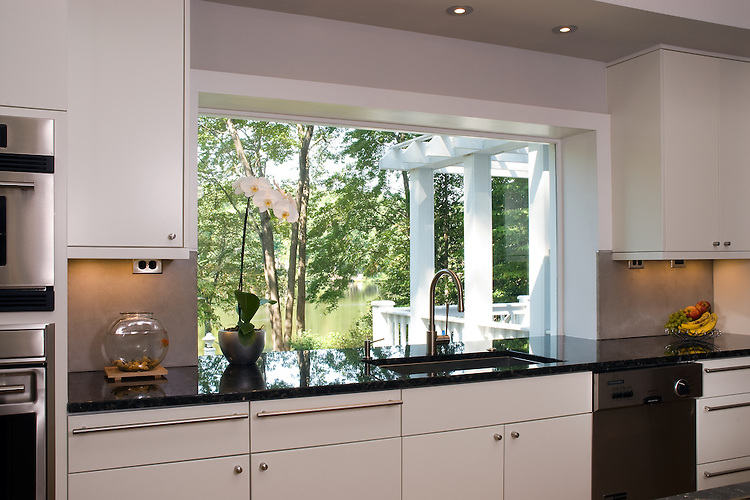 A vanishing edge countertop with a picture window overlooking a view of the lake in this contemporary kitchen.