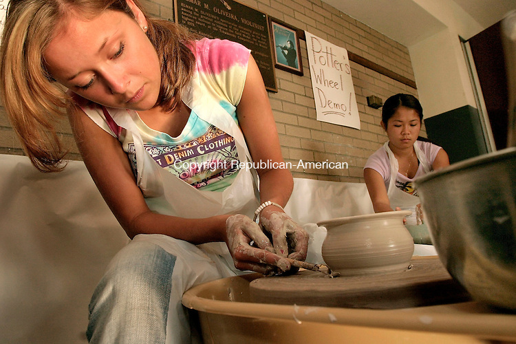 NAUGATUCK, CT - 01 JUNE 2005 -060105JS06--Naugatuck High School Clay III student Lauren Coddington, left, shapes a piece of clay as she and fellow student Arauanh Ackharath, right, participate in a potter's wheel demonstration during the Naugatuck High School art exhibit sponsored by the school's art department Wednesday.   --Jim Shannon Photo--Arauanh Ackharath; Naugatuck High School,Lauren Coddington are CQ