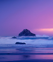 769550452v storm surf crashes against a lone sea stack at sunset in late evening pink light along bandon beach on the central oregon coast of the pacific ocean