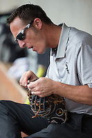 Winston-Salem Dash trainer Josh Fallin fixes a broken string on a glove during the game against the Wilmington Blue Rocks at BB&T Ballpark on July 29, 2015 in Winston-Salem, North Carolina.  The Dash defeated the Blue Rocks 5-4 in game one of a double-header.  (Brian Westerholt/Four Seam Images)