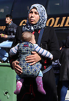 Pictured: A mother with her young child at the road block Tuesday 23 February 2016<br /> Re: Migrants on their way back to Athens have been caught by the blocked off motorway at Tembi, where local farmers have closed off the road, protesting against pension and welfare reforms near Trikala, Greece.