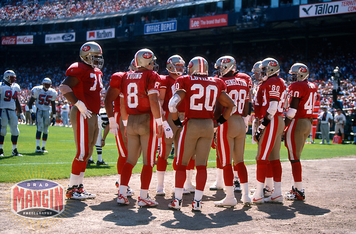 SAN FRANCISCO, CA:  Quarterback Steve Young of the San Francisco 49ers in a huddle with his offense during a game against the New England Patriots at Candlestick Park in San Francisco, California on September 17, 1995. (Photo by Brad Mangin)