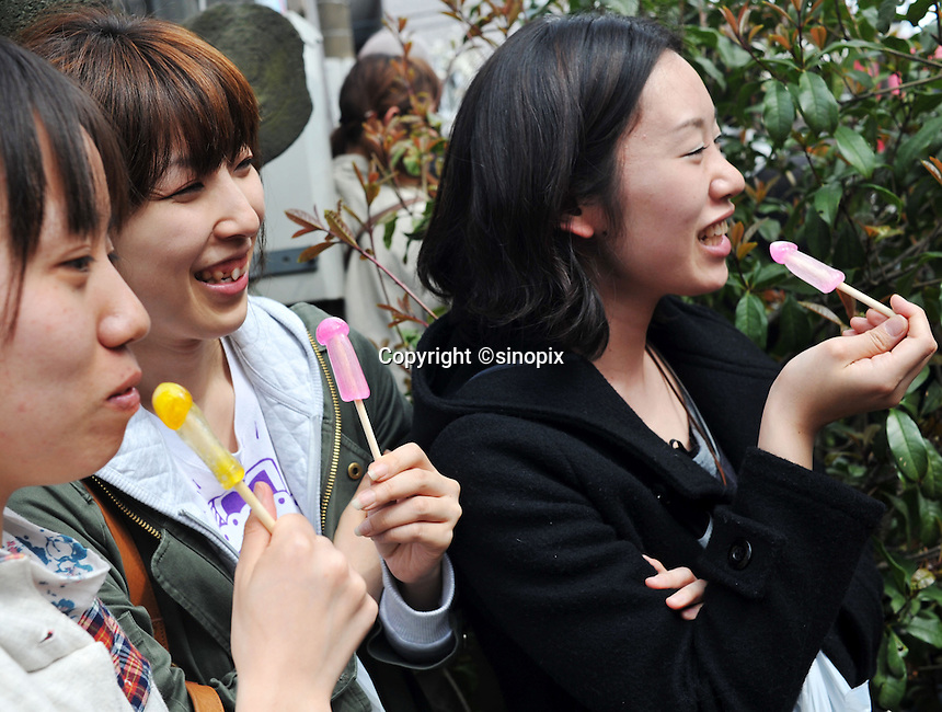 Gils suck penis pops at the penis festival in Japan during which a huge pink penis is carried through the streets of Kawasaki at the Kanamara Matsuri (Festival of the Steel Phallus) 05 April 2009.   The shinto festival dating back to the edo period350 years ago, has it's roots where prostitutes prayed not only that business would be brisk, but for protection from syphilis.  With the spread of syphilis now curbed, participants in the modern festival solicit donations for HIV/AIDS research.