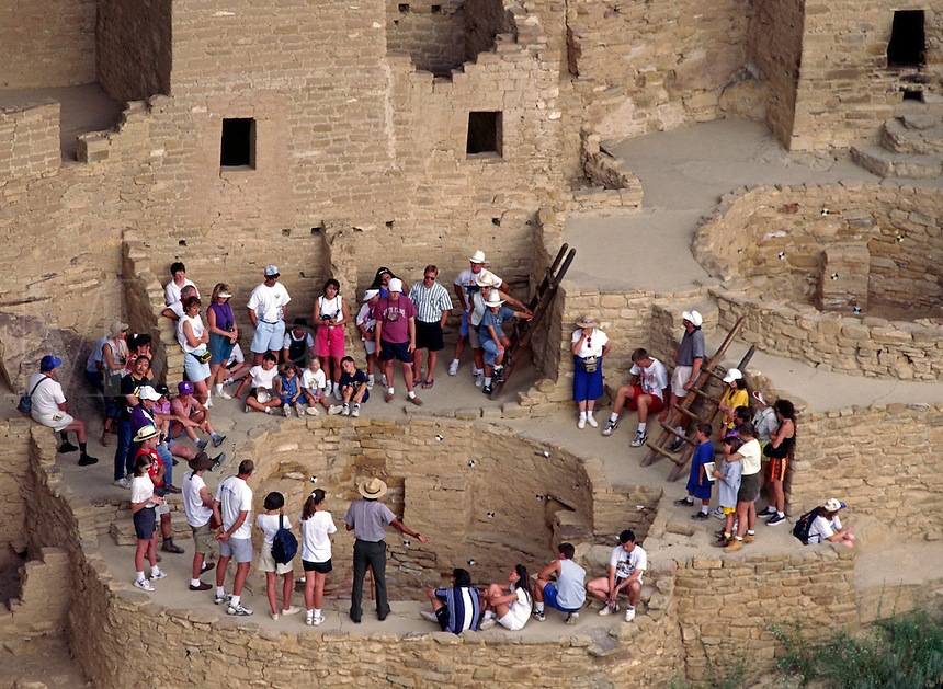 Visitors encircle a KIVA at CLIFF PALACE,  the most extensive ANASAZI ruin of MESA VERDE NP .