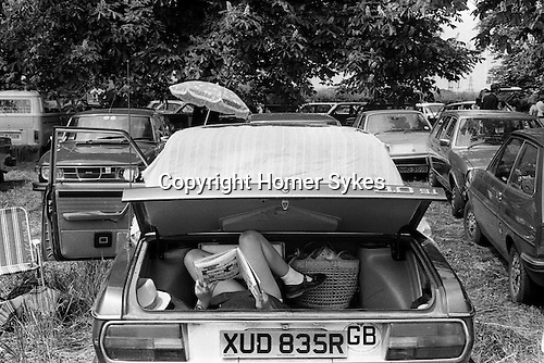 Child reading a comic in car boot. Eton College 4th of June Parents Day. England.