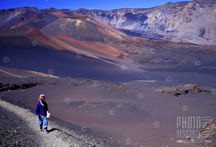 A small boy walks the moonlike multicolored Sliding Sands trail inside Haleakala Crater on the island of Maui.