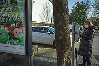 "Switzerland. Canton Ticino. Lugano. An elderly woman wears a mask on the face to protect herself from the Coronavirus (also called Covid-19). She checks the latest news on her smartphone. On a Coop poster, the new campaign to earn a Coop Brico+Loisirs gift card or a set of gardening tools. Cars' parking. Due to the spread of the coronavirus, the Federal Council has categorised the situation in the country as ""extraordinary"". It has issued a recommendation to all citizens to stay at home, especially the sick and the elderly. The Federal Council (German: Bundesrat, French: Conseil fédéral, Italian: Consiglio federale, Romansh: Cussegl federal) is the seven-member executive council that constitutes the federal government of the Swiss Confederation. Coop is one of Switzerland's largest retail and wholesale companies. It is structured in the form of a cooperative society with around 2.5 million members. 17.03.2020 © 2020 Didier Ruef"